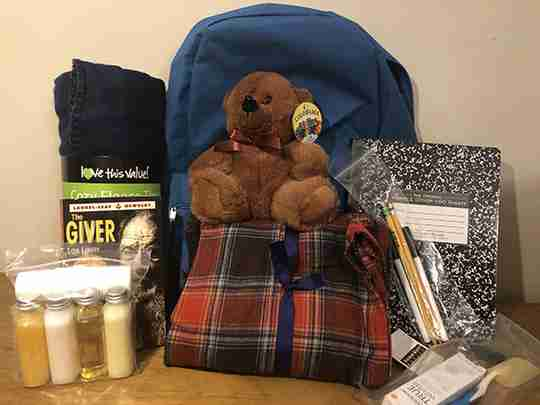 Brown bear in a backpack with a lot of supplies.