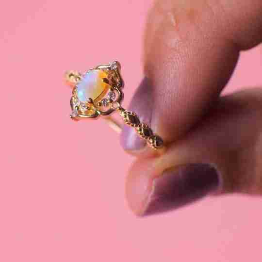 A Blue Opal Carved Ring on a pink background