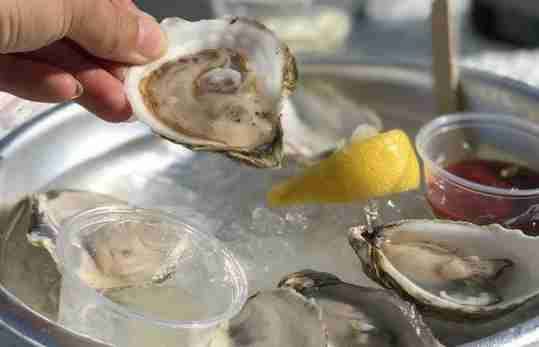 Person Eating Oysters Lemon Red Sauce