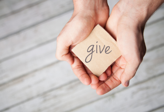 Hands with the word give on paper