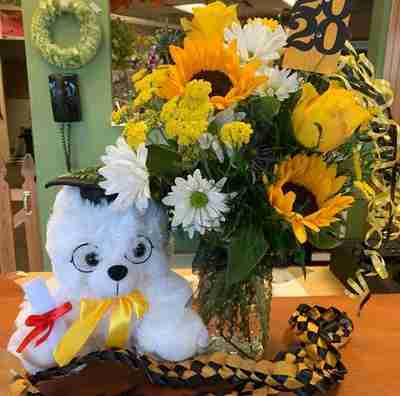 A white graduation bear sitting next to a bouquet of dandelions in a vase