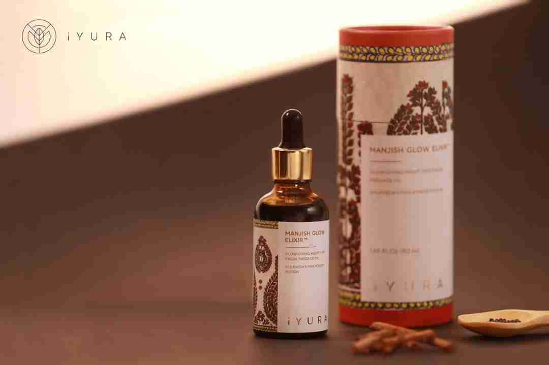 a beautiful photo of Manjish Glow Elixir - iYURA's bestselling night oil - accompanied by its beautifully illustrated, protective cylinder packaging