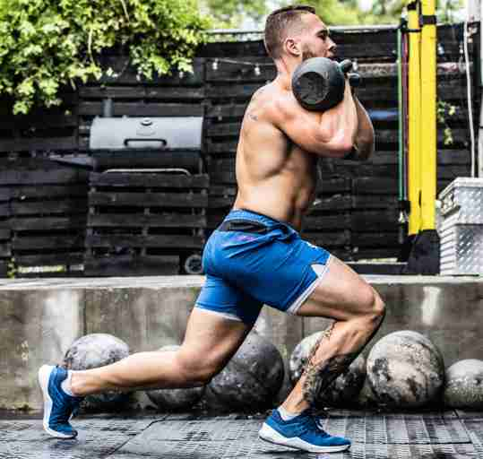 A male CrossFit athlete working out with kettlebells during his periodization training.