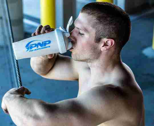 A CrossFit athlete drinking a carbohydrate supplement to fuel work capacity.