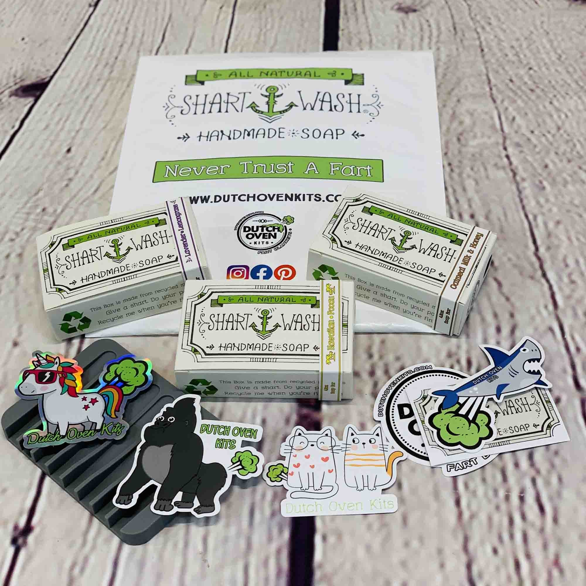 picture of 3 bars of Shart Wash natural handmade soap bars, stickers, and a gray soap dish on a wood background