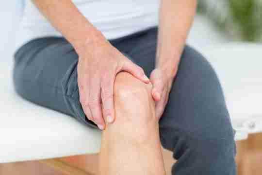 Person Grabbing Knee Symptomatic knee osteoarthritis