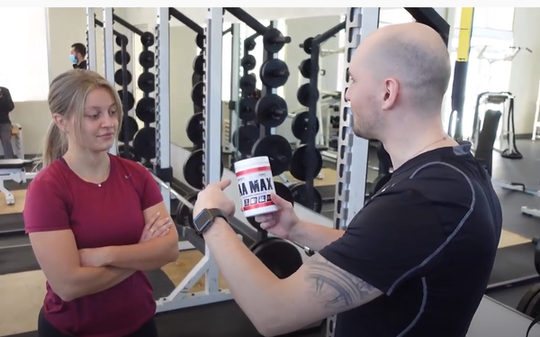 Fit Man in Black with Woman Holding Powder in Hand Gym