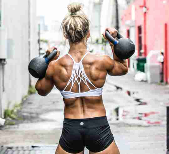 Female CrossFit athlete benefiting from creatine supplementation during her kettlebell workout.