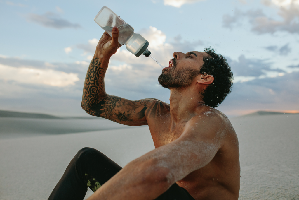 Tattooed man with no shift drinking bottled water while sitting in the sand