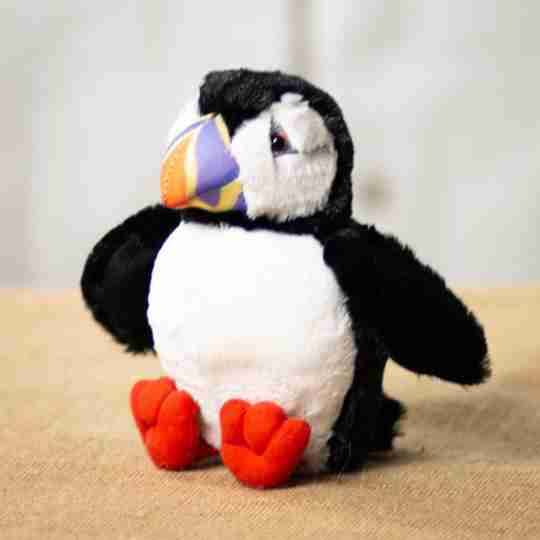 This stuffed animal puffin has black and white fur with an orange and purple beak.