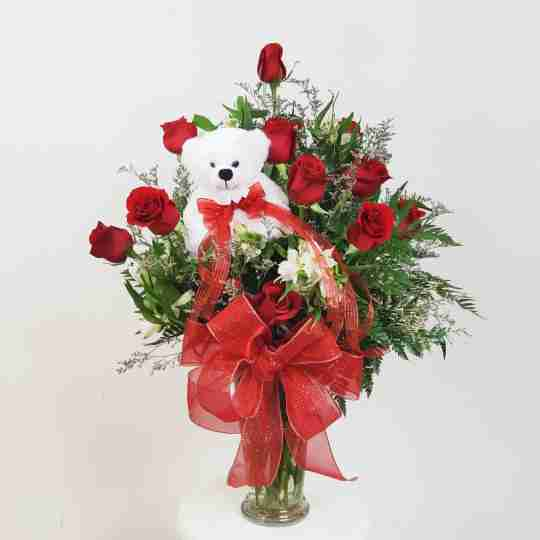 A white bear in a vase of roses