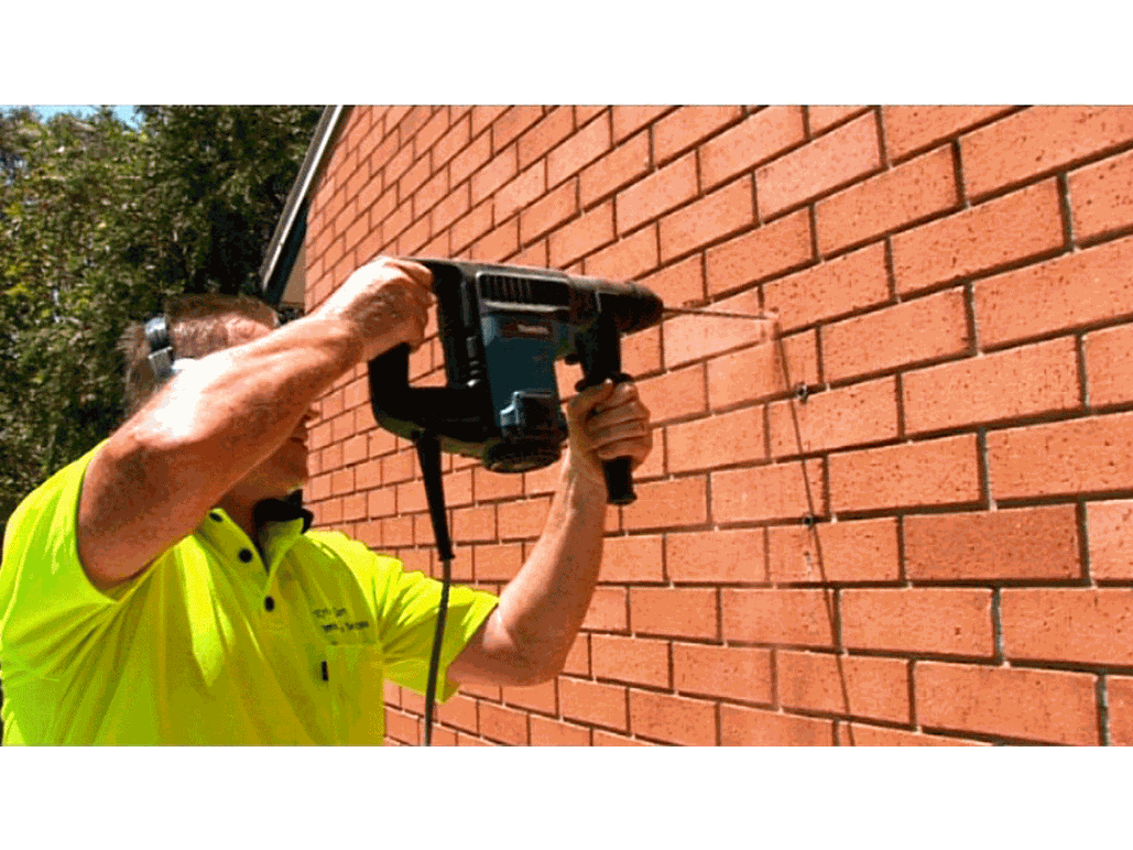 clothesline installation and supply with installer drilling into brick wall to mount clothesline