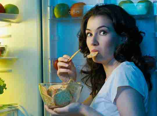 Woman Eating Food From Fridge Looking at Camera Surprised