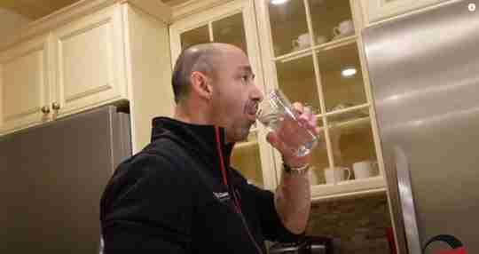 Man Drinking Water in Glass in Kitchen