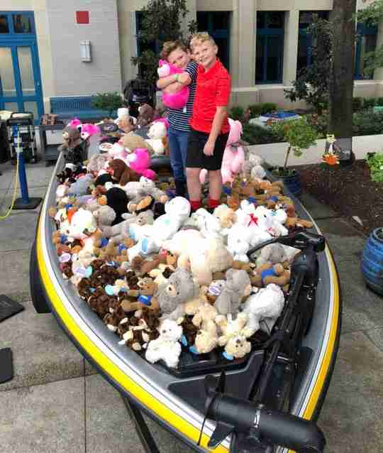 Two kids standing in a boat on land that's filled with stuffed animals.
