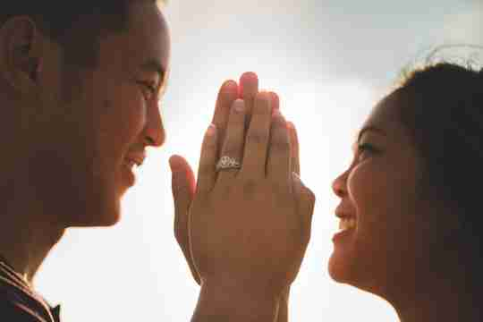 A couple smiling at each other, holding their hands up between them, an engagement ring on the woman's hand.