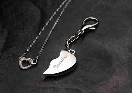 Two sterling silver necklaces, one of them bearing a heart-shaped outline, and the other is one-half of a heart with an engraved name on it.