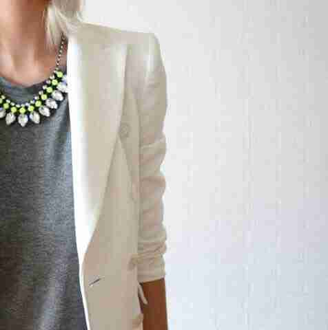 gir in grey inner and white blazer wearing yellow green necklace
