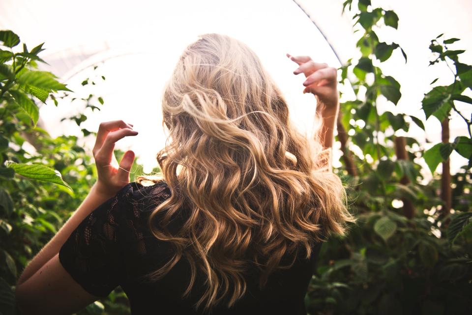 A woman with beautiful hair in a tall shrub garden.