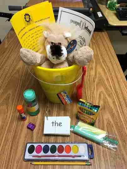 A beige lion in a bucket surrounded by school supplies