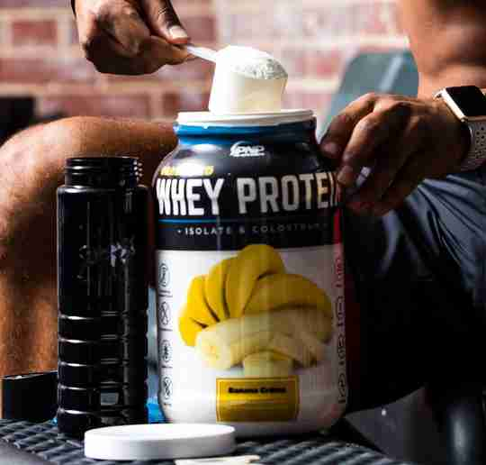 Athlete taking a scoop of Grass-Fed Whey Protein Isolate and Colostrum post-workout.
