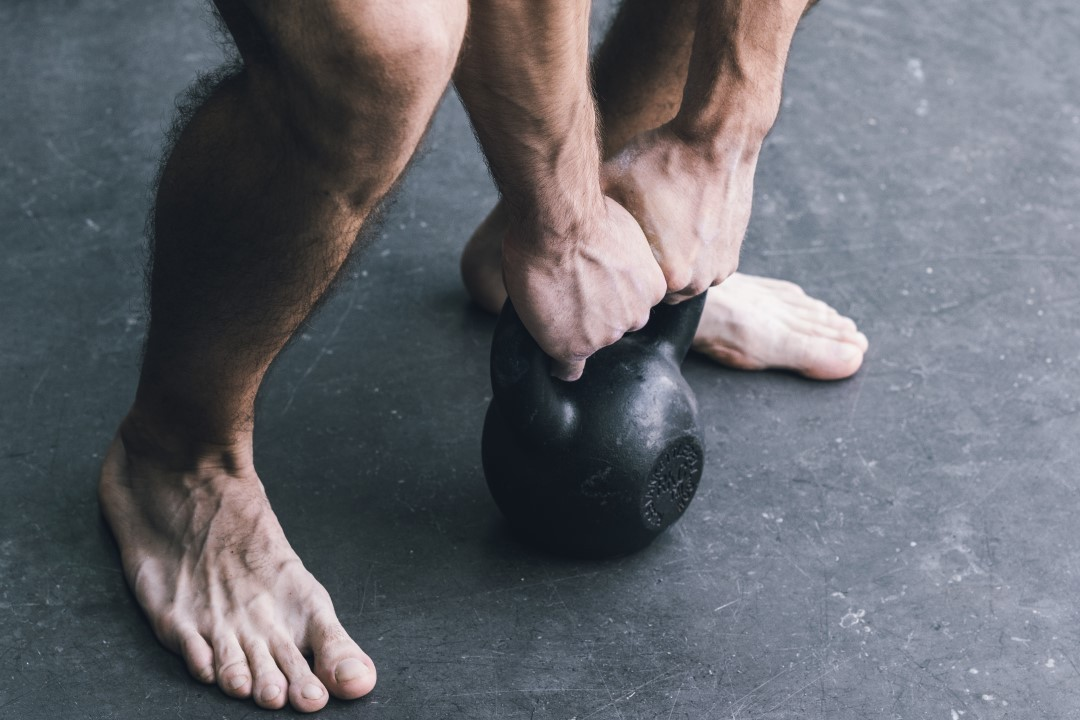 A male athlete workout barefoot with a kettlebell.A male athlete workout barefoot with a kettlebell.A male athlete workout barefoot with a kettlebell.