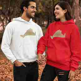 A couple holding hands wearing matching hoodies. One hoodie is red the other white