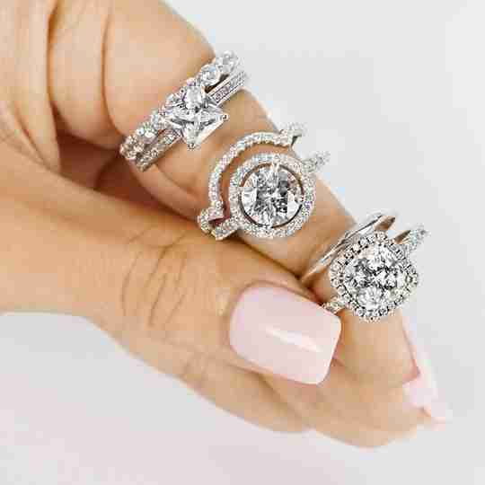 A woman holding three bridal ring sets from Brilliance.com