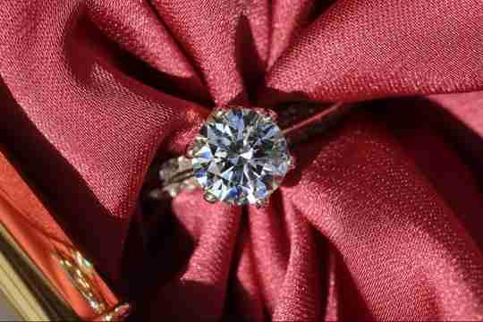 Round cut brilliant diamond on red fabric background