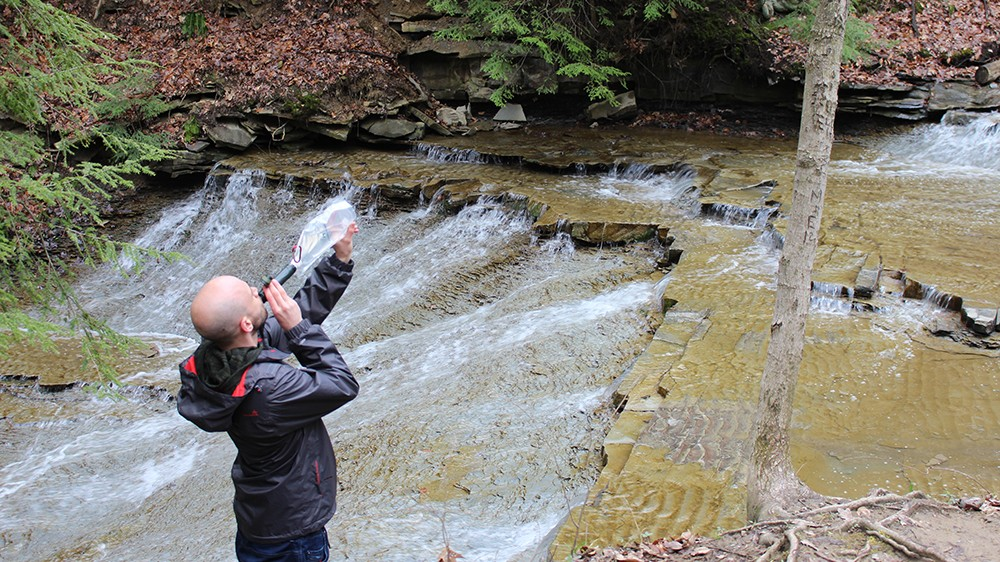 A hiker uses the Survivor Filter Squeeze Kit on a hike through Cuyahoga Valley National Park