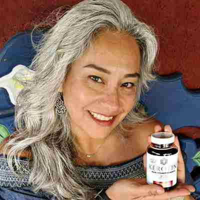 Model With Long Gray Hair Holding a Bottle of Kerotin Hair Vitamin Gummies