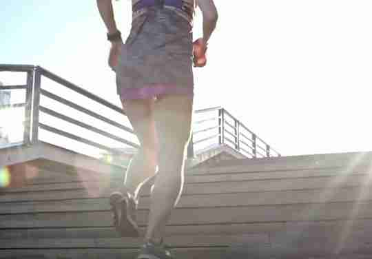 Fit Woman Running Up Stairs Outside Sunny Day