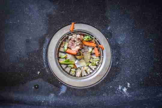 food waste and scraps sitting at the bottom of a sink drain in the metal catcher