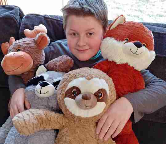 A young boy holding a bunch of stuffed animals