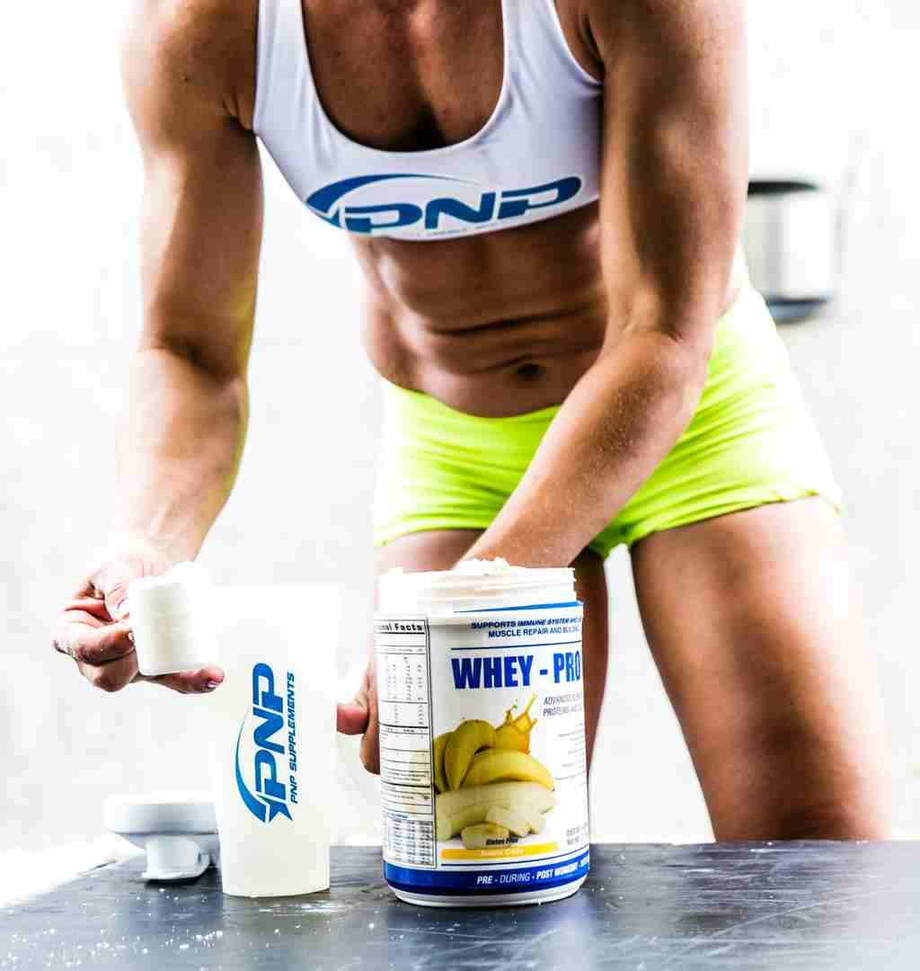 CrossFit athlete Luisa Porras scooping the best whey protein for post workout recovery.