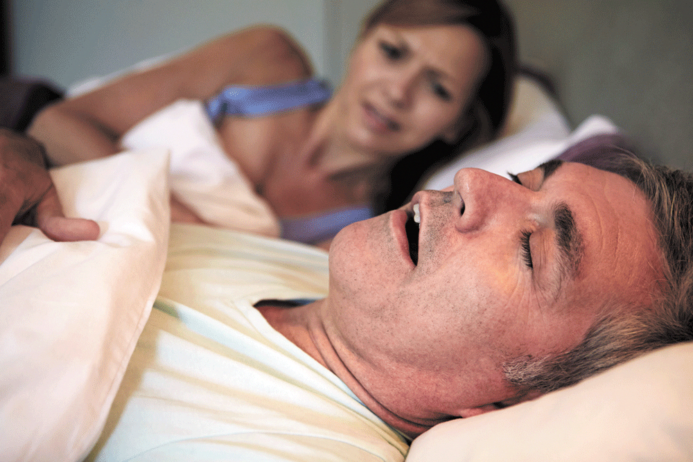 recently sleeping woman frustrated as her husband snores