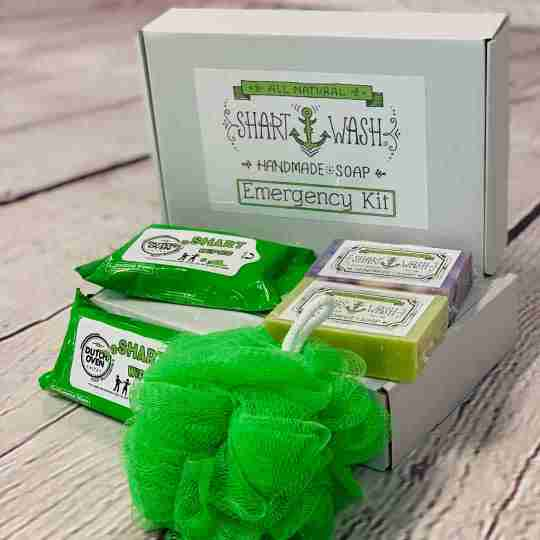 picture of shart wash emergency kit gift box with 2 green packs of shart wipes hand and surface wipes, 2 bars of shart wash soap (assorted colors) and 1 green loofah