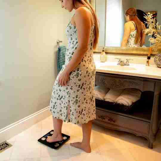 Woman in Dress On Scale In Bathroom