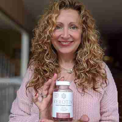 Model With Long Curly Hair Holding Kerotin Vitamin Gummies