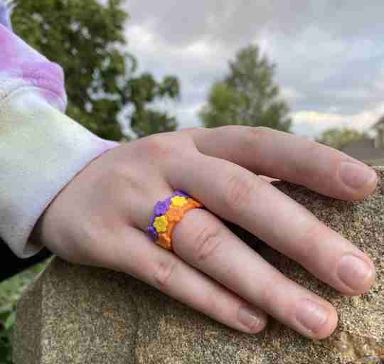 Hand resting on rock while wearing promise garden silicone ring bundle