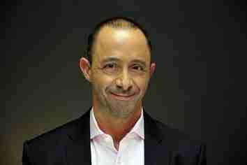 Derek Alessi Man in Suit Smiling Dark Background