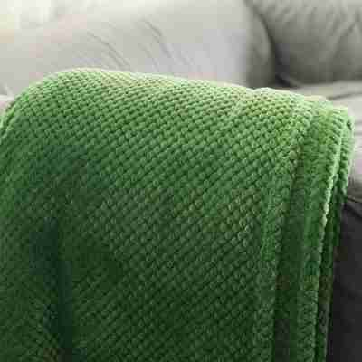 picture of a dark green blanket draped over the arm of a couch