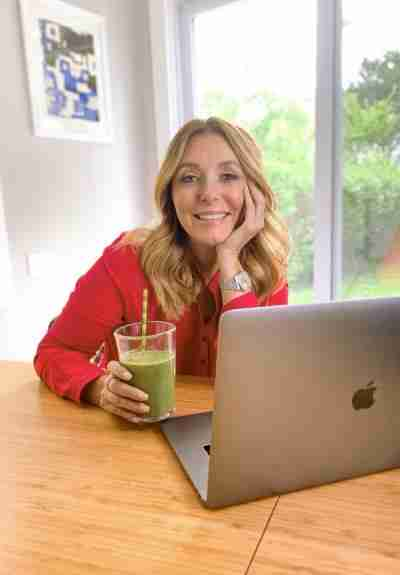 Dr. Kellyann sitting in front of MacBook with a green smoothie