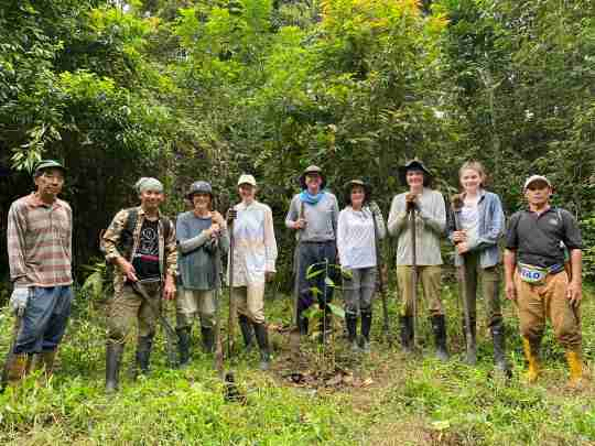 Group of 9 people standing in the forest after planting trees.