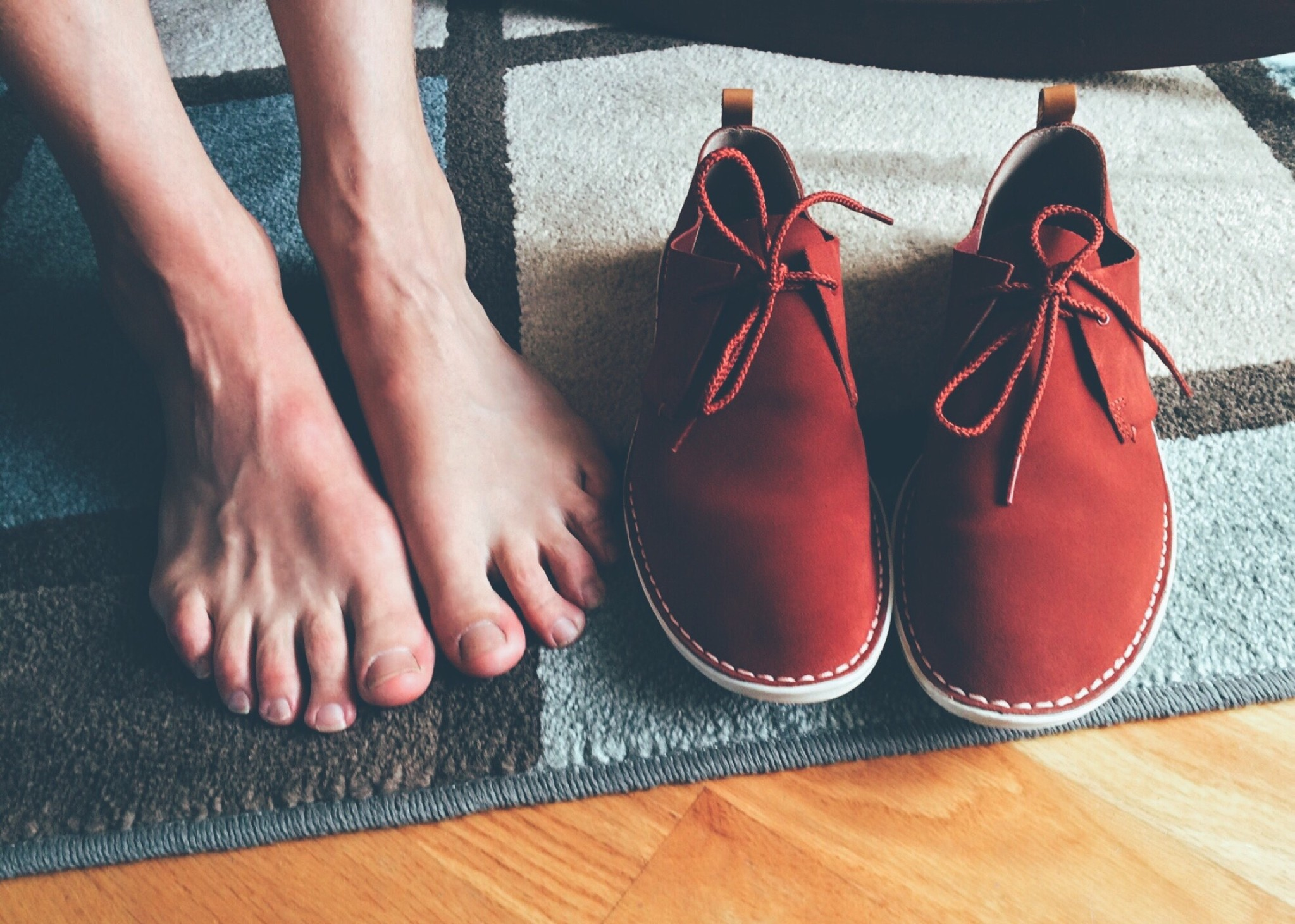 beautiful feet and red shoes placed on a mat