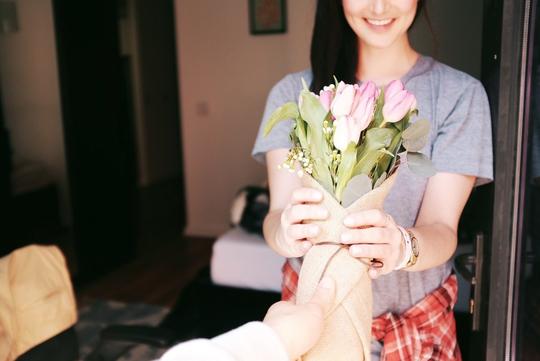 A woman receiving flowers at her door