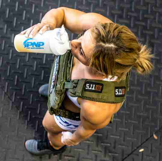 CrossFit athlete drinking a creatine supplement drink with Recover Surge by PNP Supplements.