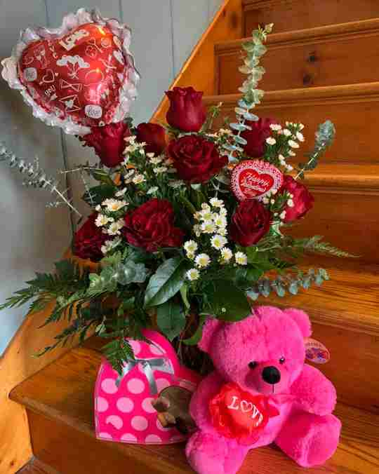 A pink bear next to a box of chocolates and roses