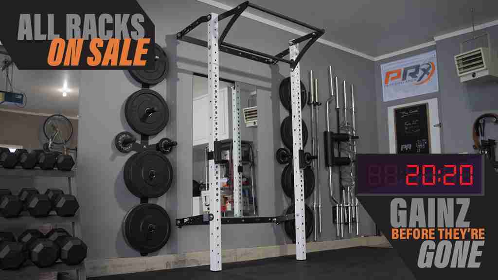 PRx White PRO rack with kipping bar, set up in a full garage gym, with graphics over that say