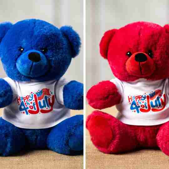 A 9 inch from head to bottom red and blue Colorama Bear that's wearing a festive white 4th of July shirt